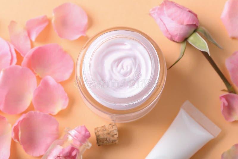 Bella composizione con i petali della crema per il corpo e del fiore sul fondo di colore fotografie stock