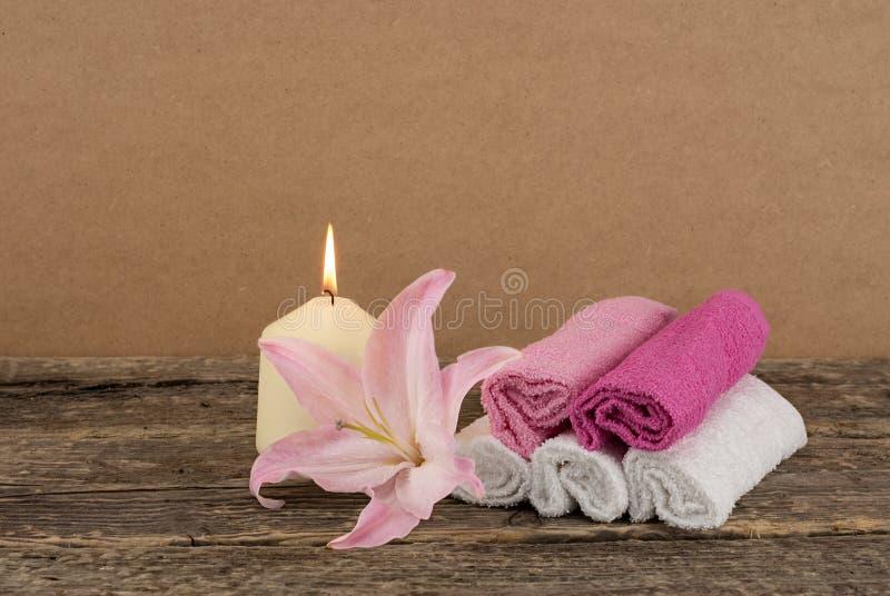 Bella composizione con la candela, il fiore rosa del giglio e gli asciugamani della stazione termale su fondo di legno fotografie stock libere da diritti