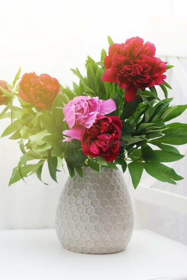 Bella composizione rosa-rosso nella primavera del mazzo del mazzo dei fiori della peonia in vaso ceramico modificato immagine stock