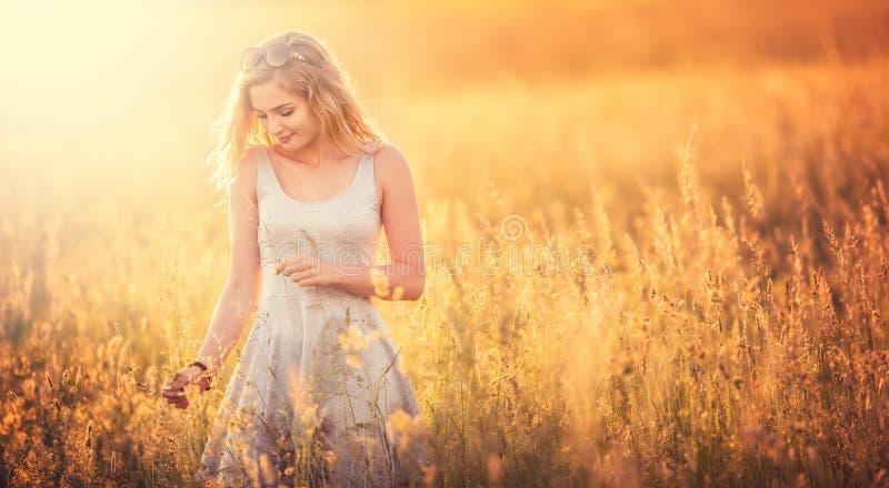 Bella condizione bionda tenera della ragazza al prato di estate in prendisole grige Donna felice libera che gode della natura immagine stock