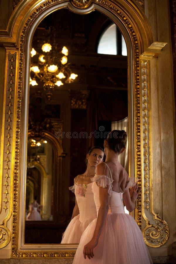 Bella condizione della ballerina davanti allo specchio su fondo dell'interno lussuoso fotografie stock