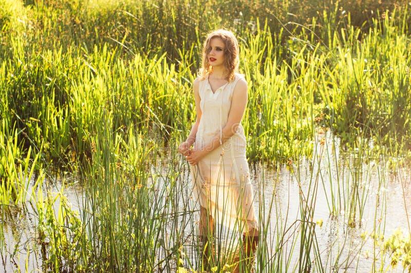 Bella condizione della ragazza nel centro del fiume e schiacciare il vestito fotografia stock