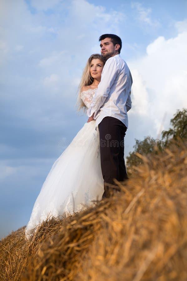 Bella condizione della sposa e dello sposo delle coppie nel fieno contro il cielo immagini stock libere da diritti