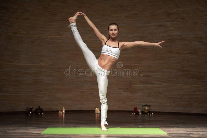 Bella condizione esile della giovane signora sulla stuoia di yoga nei vestiti e nella chiusura di sport dei suoi occhi mentre met immagini stock
