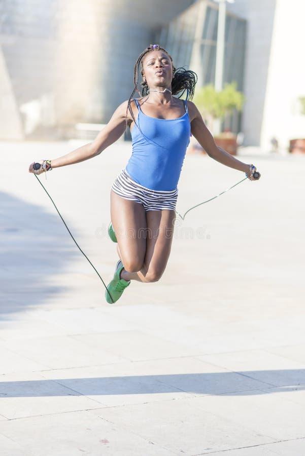 Bella corda di salto africana della donna di sport, stile di vita sano co fotografia stock