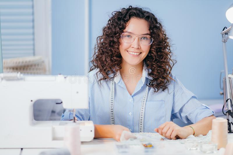 Bella cucitrice che esamina macchina fotografica e che lavora con le perle fotografia stock libera da diritti