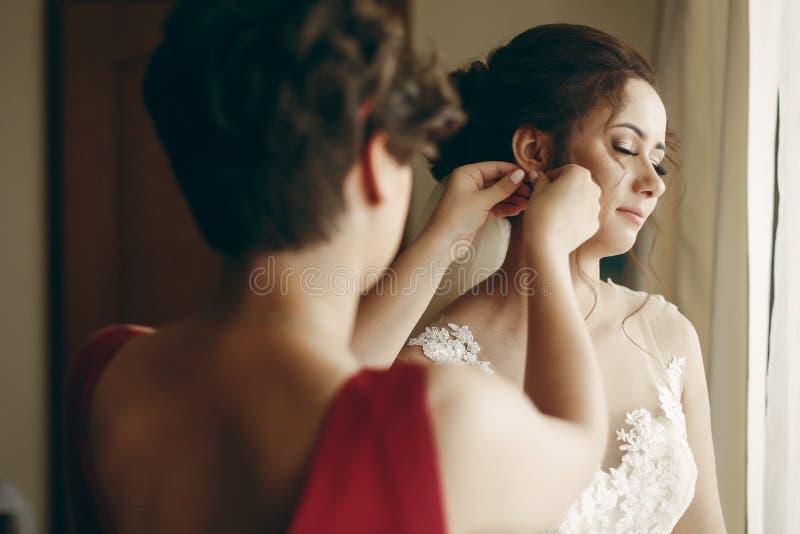 Bella damigella che aiuta la sposa brunette in abito bianco da sposa messa sugli orecchini di lusso, preparazione mattutina al ma fotografia stock