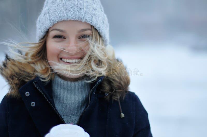 Bella donna in abbigliamento di inverno con la tazza del outdoo caldo del caffè immagini stock libere da diritti