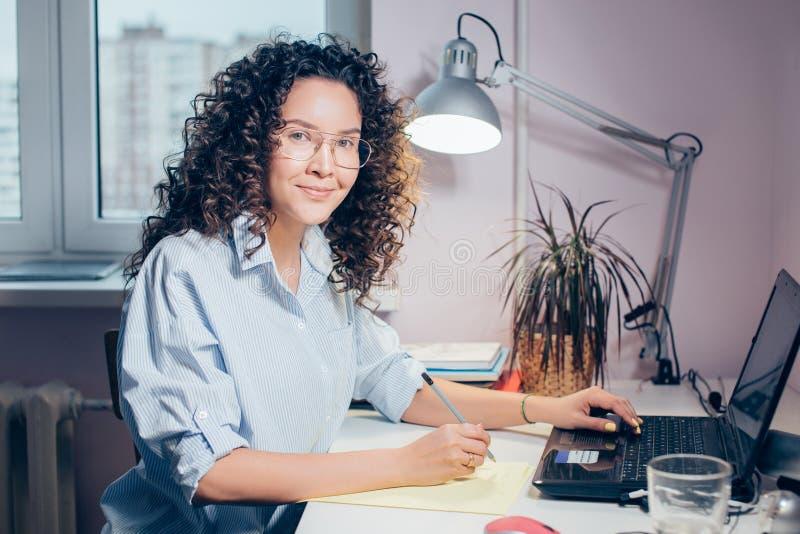 Bella donna abbronzata con il computer portatile che posa alla macchina fotografica fotografie stock