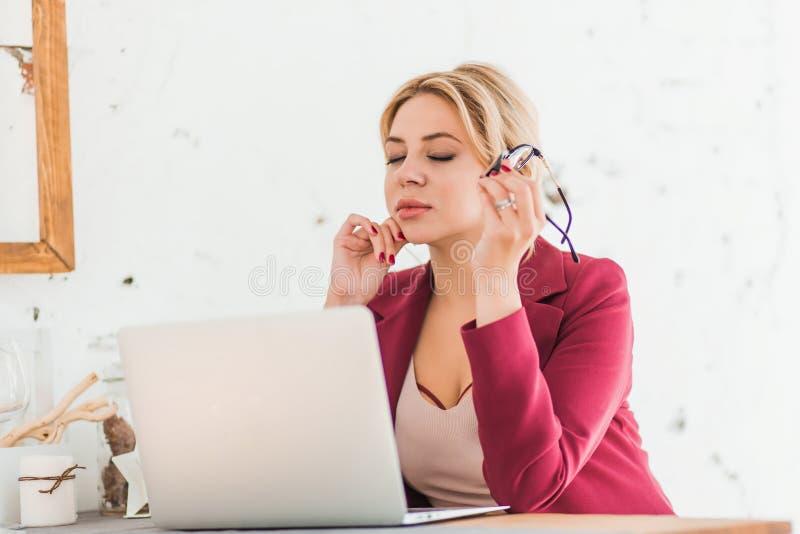Bella donna abile di affari che si siede alla tavola alla stazione di lavoro con il computer portatile fotografie stock libere da diritti