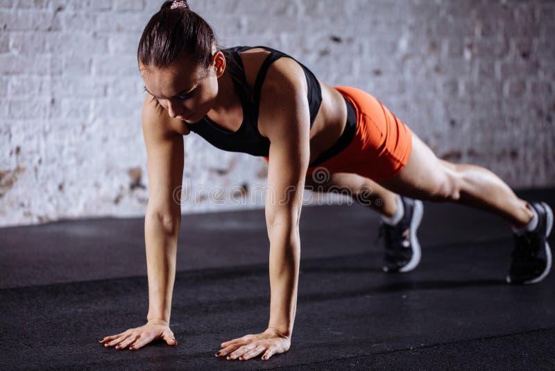 Bella donna in abiti sportivi che fanno plancia mentre trainnig alla palestra adatta dell'incrocio fotografia stock libera da diritti