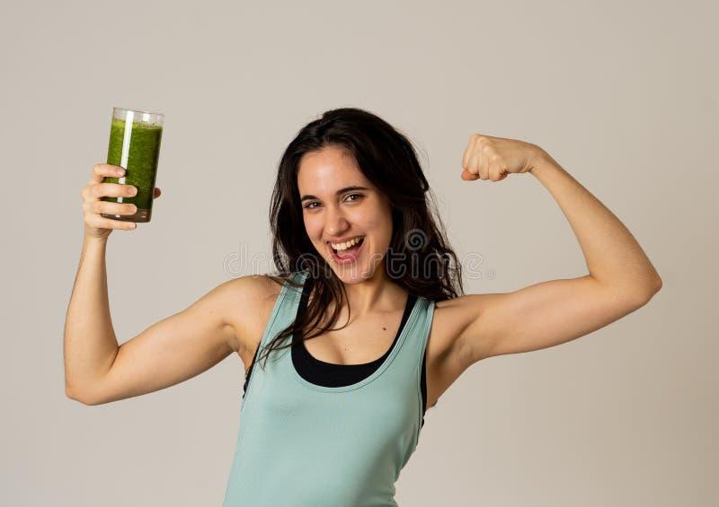 Bella donna adatta del Latino di sport che beve il frullato sano di verdura fresca che ritiene grande e sano immagine stock