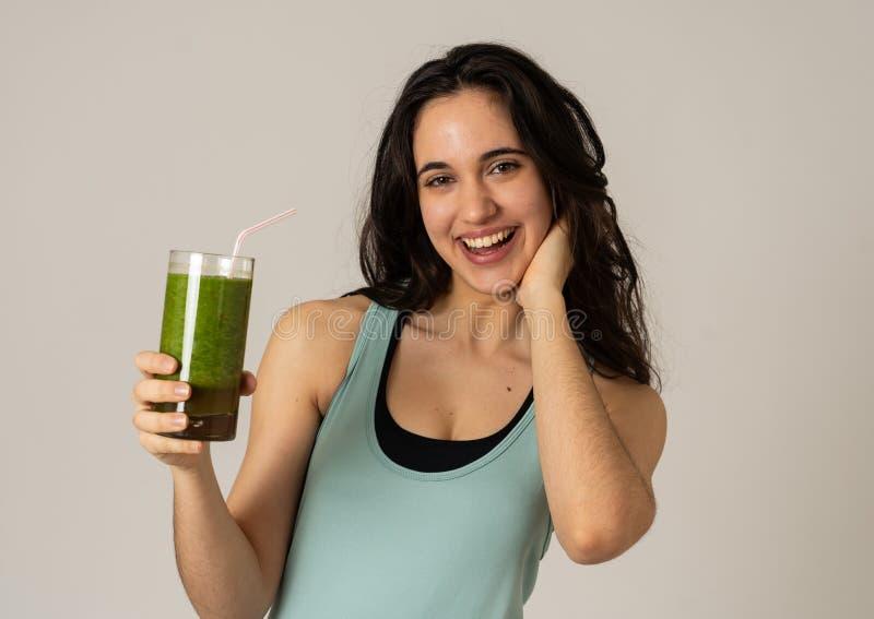 Bella donna adatta del Latino di sport che beve il frullato sano di verdura fresca che ritiene grande e sano immagini stock libere da diritti