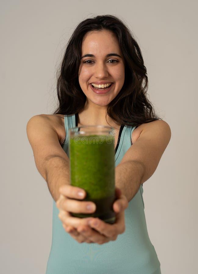 Bella donna adatta del Latino di sport che beve il frullato sano di verdura fresca che ritiene grande e sano immagini stock