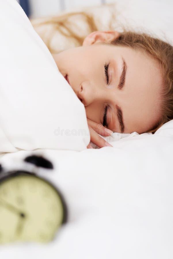 Bella donna addormentata con la sveglia. fotografia stock libera da diritti