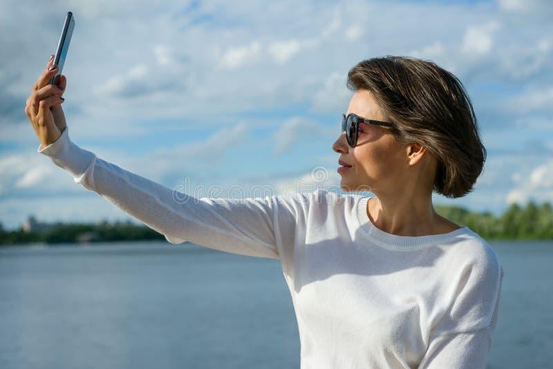 Bella donna adulta che fa selfie facendo uso dello smartphone fotografie stock libere da diritti
