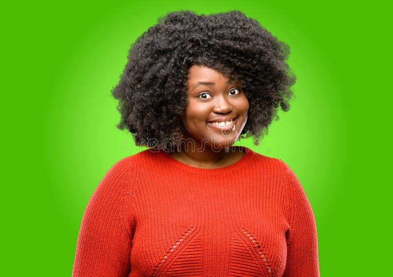 Bella donna africana con capelli ricci isolati sopra fondo verde immagini stock libere da diritti