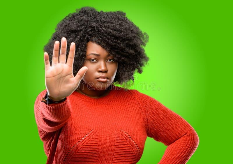 Bella donna africana con capelli ricci isolati sopra fondo verde fotografie stock