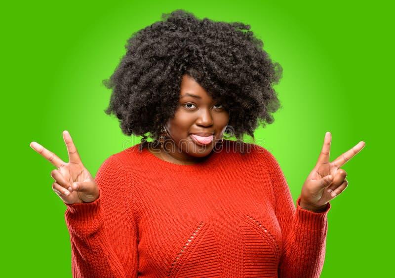 Bella donna africana con capelli ricci isolati sopra fondo verde fotografia stock