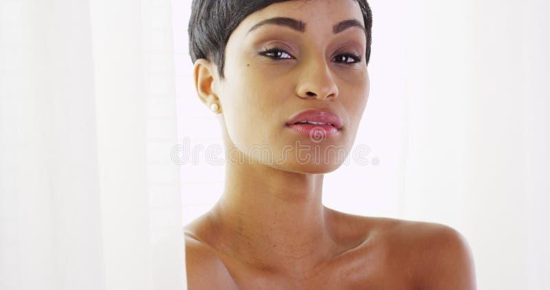 Bella donna africana topless che esamina macchina fotografica e che gioca con le tende fotografie stock libere da diritti