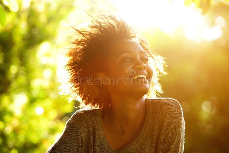 Bella donna afroamericana che sorride con il tramonto immagini stock