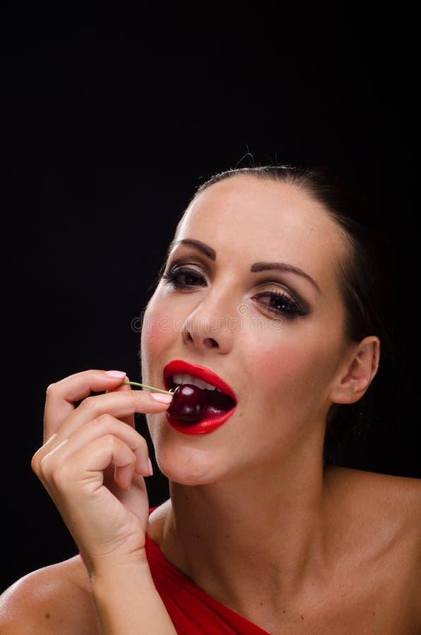 Bella, donna alla moda che mangia una ciliegia rosso scuro immagini stock libere da diritti