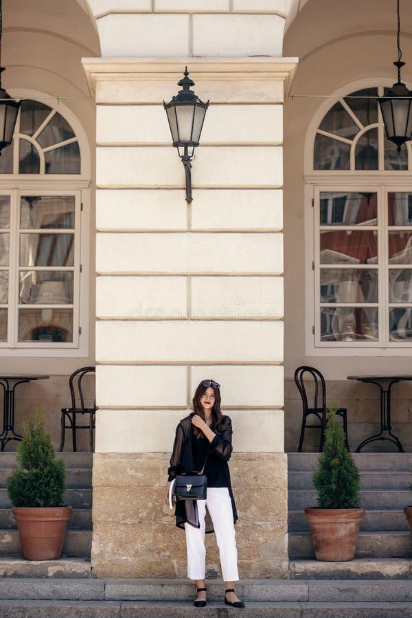 Bella donna alla moda che posa in via soleggiata della città, tenente pho fotografia stock libera da diritti