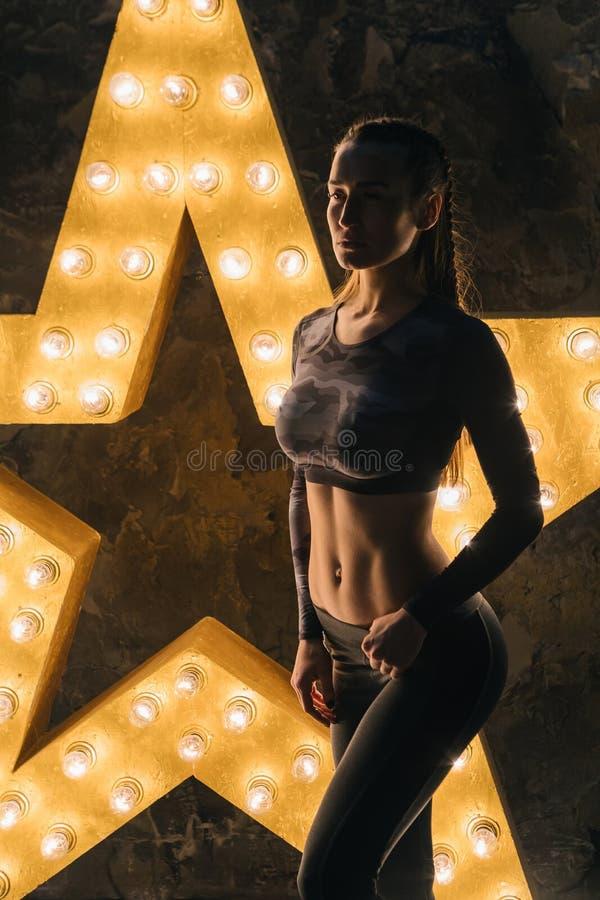 Bella donna alla moda della stella di sport Corpo adatto di stupore Stella della lampadina su fondo immagini stock libere da diritti