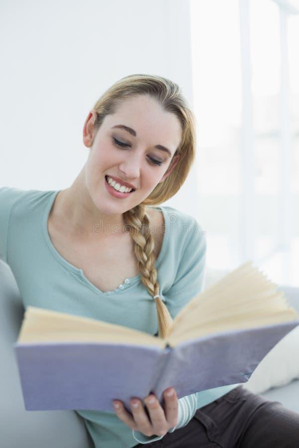 Bella donna allegra che legge un libro mentre sedendosi sullo strato fotografie stock libere da diritti
