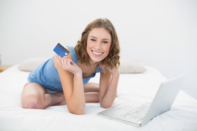Bella donna allegra che mostra la sua carta di credito mentre sedendosi sul suo letto accanto al suo computer portatile immagini stock