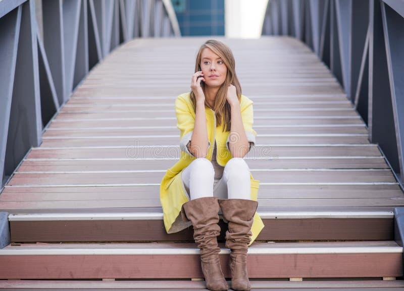 Bella donna allegra che si siede sulle scale e che parla sul telefono cellulare immagine stock