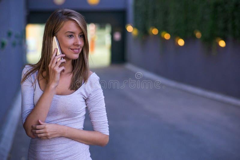 Bella donna allegra che si siede sulle scale e che parla sul telefono cellulare fotografie stock