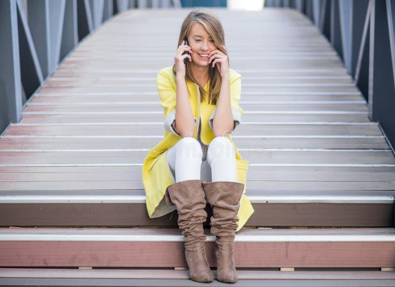 Bella donna allegra che si siede sulle scale e che parla sul telefono cellulare immagini stock