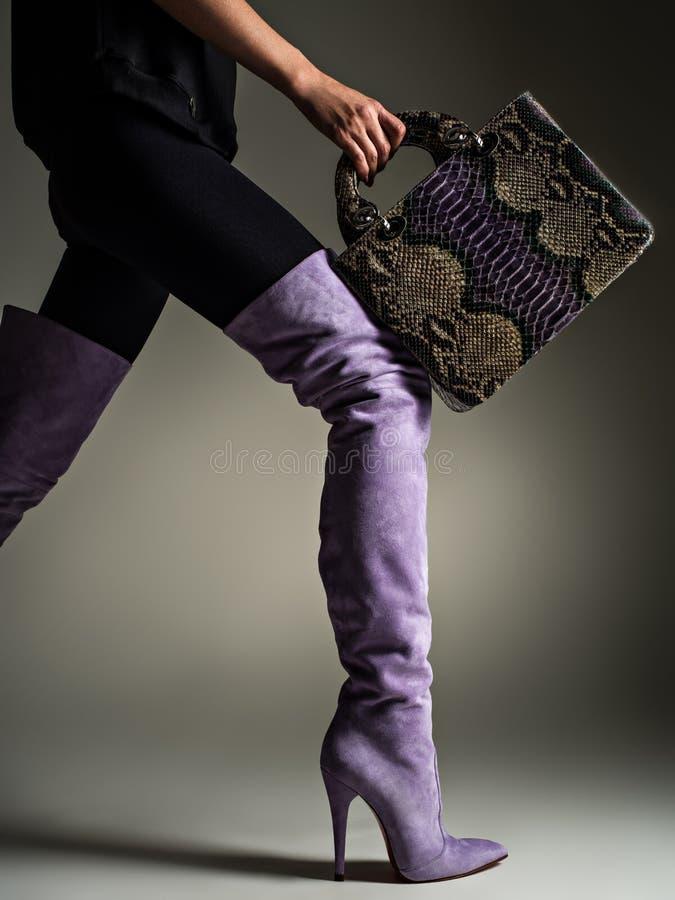 Bella donna in alti stivali porpora La ragazza alla moda tiene la borsa di cuoio viola alla moda fotografia stock
