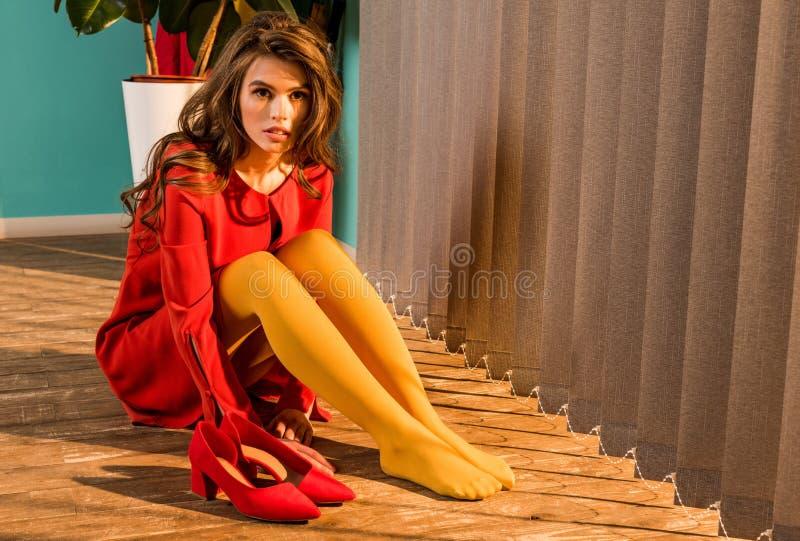 bella donna antiquata in vestito rosso che si siede sul pavimento e sul distogliere lo sguardo fotografia stock