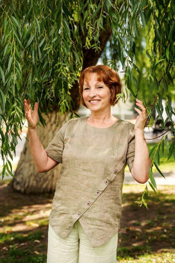 Bella donna anziana in retro vestiti d'annata di tela che spingono i rami con le foglie del salice immagine stock libera da diritti