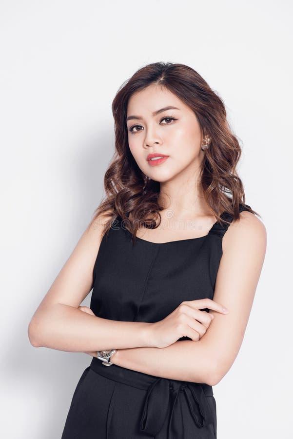 Bella donna asiatica alla moda nella posizione nera casuale elegante dell'attrezzatura immagini stock