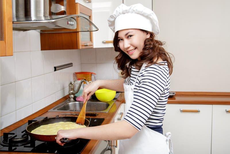 Bella donna asiatica in cappello bianco del cuoco unico che prepara un'omelette nella cucina fotografia stock libera da diritti