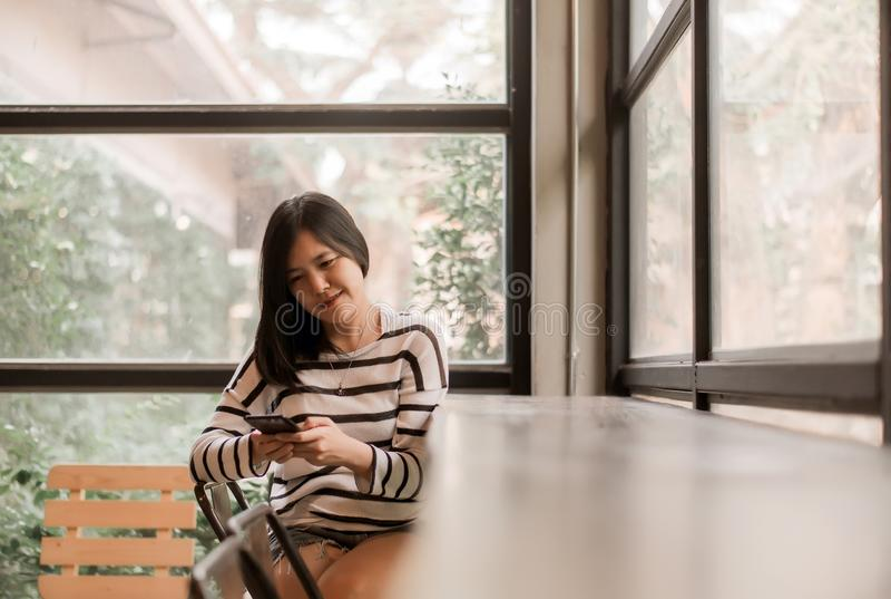 Bella donna asiatica che collega il suo smartphone con il wifi libero in caffè della caffetteria, felice e sorridente, pensiero d fotografia stock libera da diritti