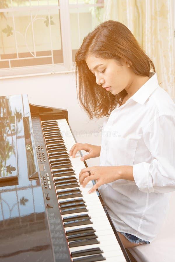 Bella donna asiatica che gioca piano fotografie stock