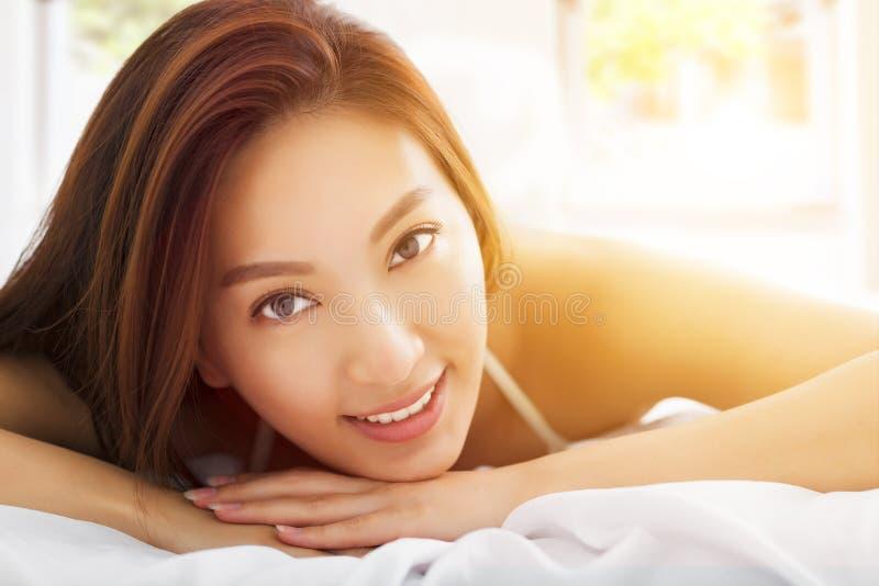 Bella donna asiatica che si rilassa sul letto con le sedere di luce solare fotografie stock libere da diritti