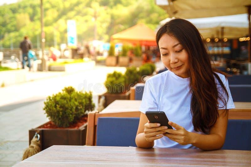 Bella donna asiatica che si siede in un caffè che sorride e che esamina lo smartphone fotografie stock libere da diritti