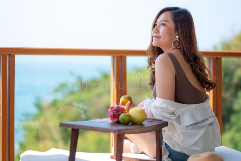 Bella donna asiatica che tiene frutti mentre goda di di sedersi al balcone con i precedenti di vista del mare fotografie stock
