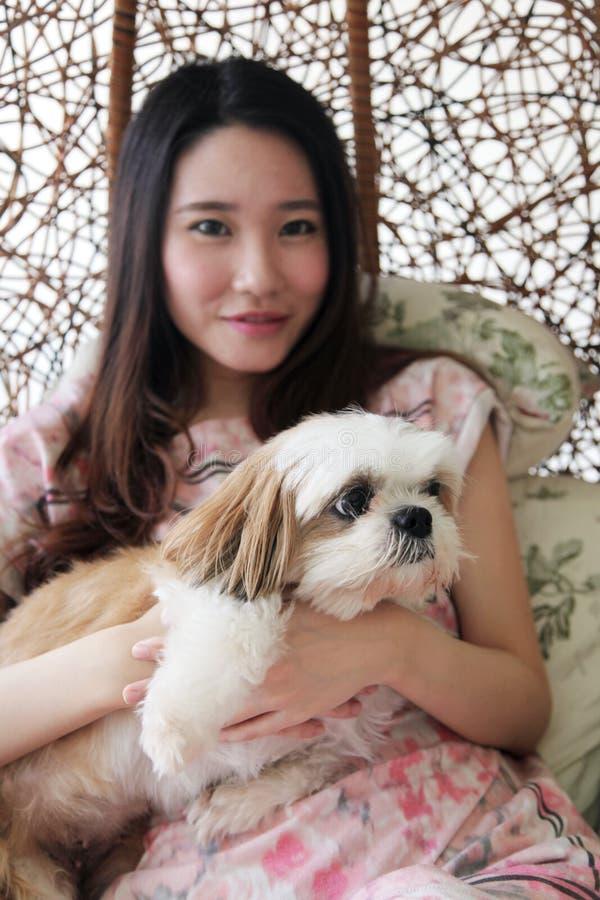 Bella donna asiatica che tiene un cane fotografia stock