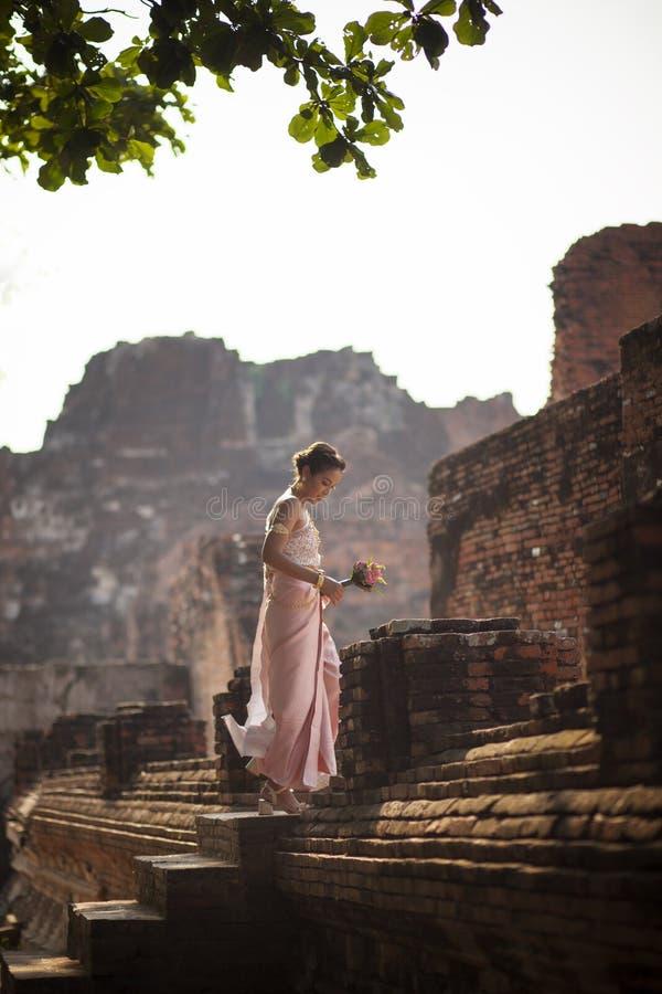 Bella donna asiatica con il fiore di loto rosa che sta su antico fotografia stock