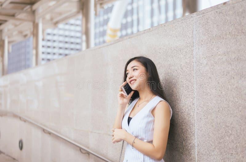 Bella donna asiatica del ritratto che per mezzo del telefono cellulare e camminando nella città concentrare, felice e nel sorride immagini stock libere da diritti