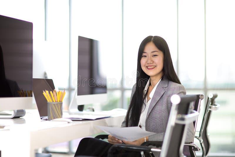 Bella donna asiatica di affari che si siede e che sorride sulla sedia nella m. immagine stock libera da diritti