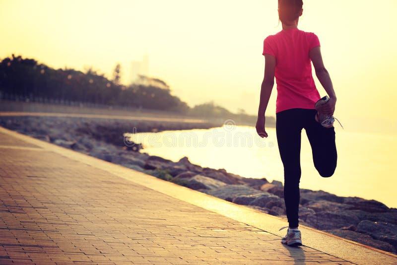 Bella donna asiatica di stile di vita sano che allunga le gambe prima dell'correre immagine stock libera da diritti