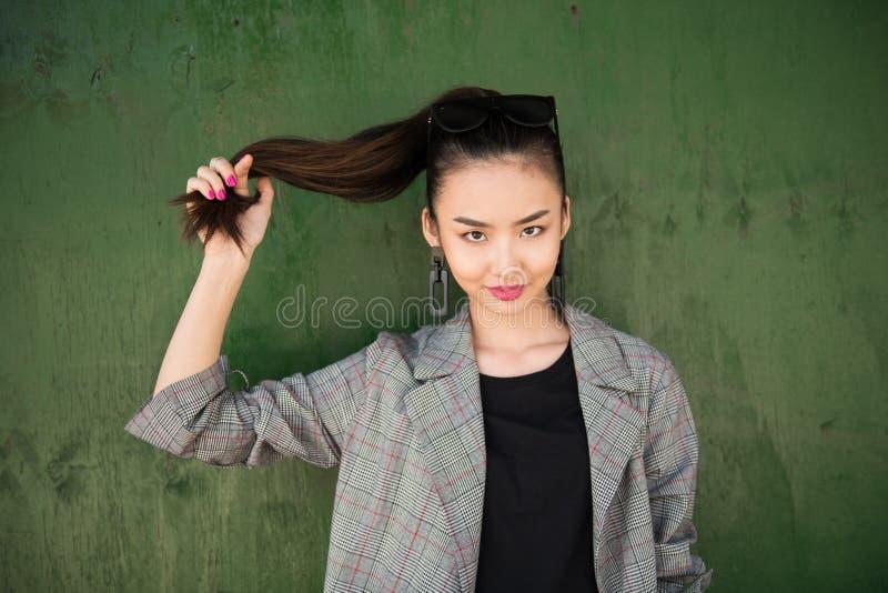 Bella donna asiatica divertendosi e tenere i suoi capelli a disposizione che sorridono fotografie stock