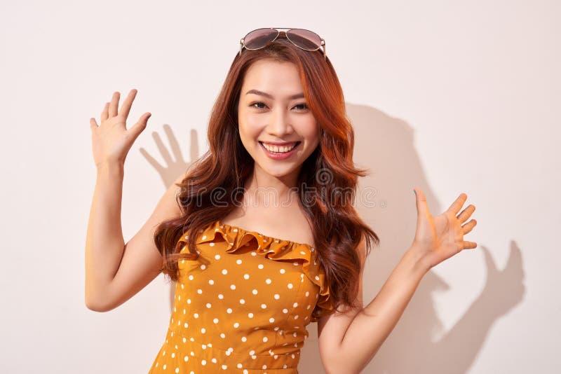 Bella donna asiatica emozionante con le mani su Sorridendo ed esaminare la macchina fotografica fotografia stock libera da diritti